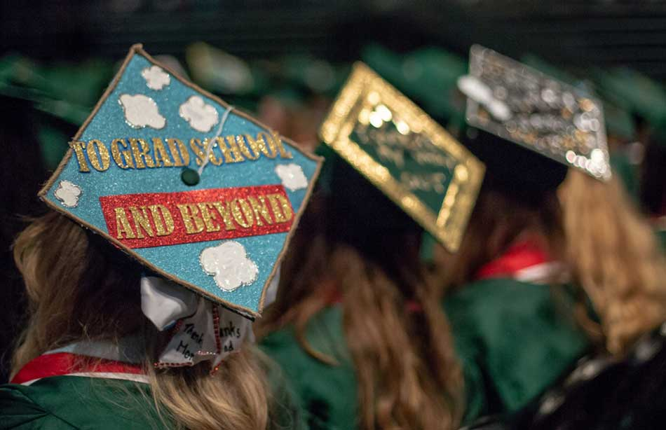 Student at commencement with a mortarboard that says To Grad School and Beyond