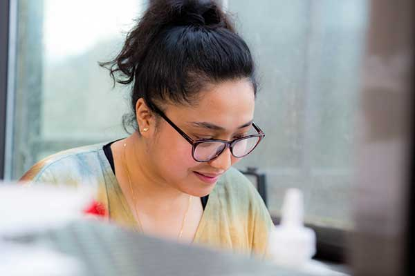 Dristi Manandhar, a UO grad student pursuing her master's in architecture from Nepal, working on a computer